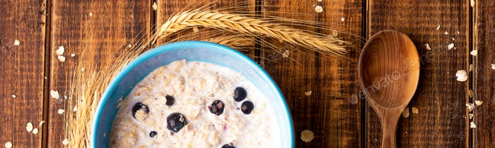 Banner of Oatmeal with currant in blue bowl with spoon