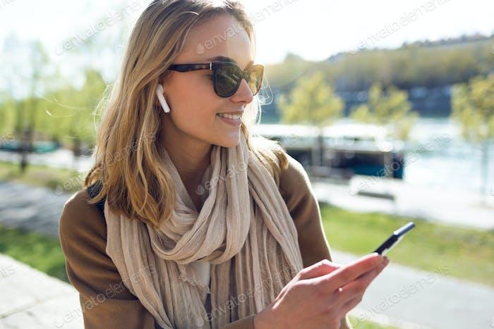 Довольно молодая женщина слушает музыку с беспроводными наушниками