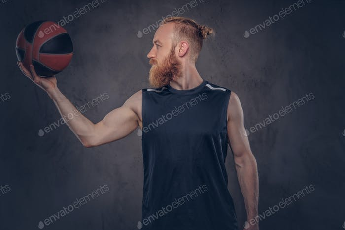 Portrait of a redhead basketball player in a black sportswear holding ball