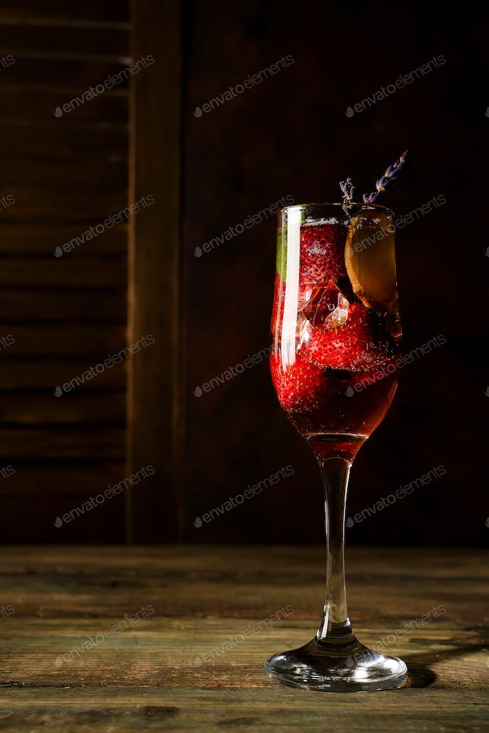 strawberry jive cocktail with ice and lavender on wooden background
