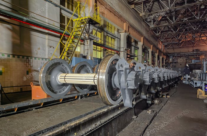 Many spare railway metro wheels on the rail inside repair plant