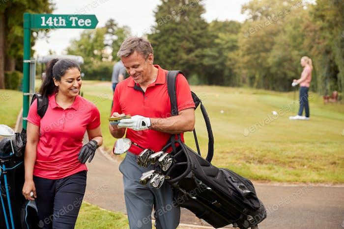 Reife paar spielen Runde der golf tragen golf taschen und markierung scorecard