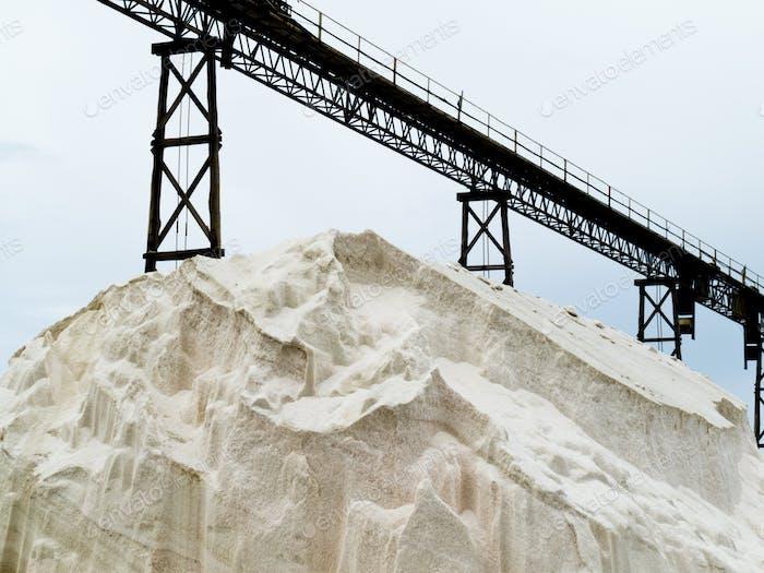 Stapel von Meersalz unter Förderband der Salzraffinerie