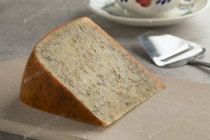 Piece of old mature cumin cheese