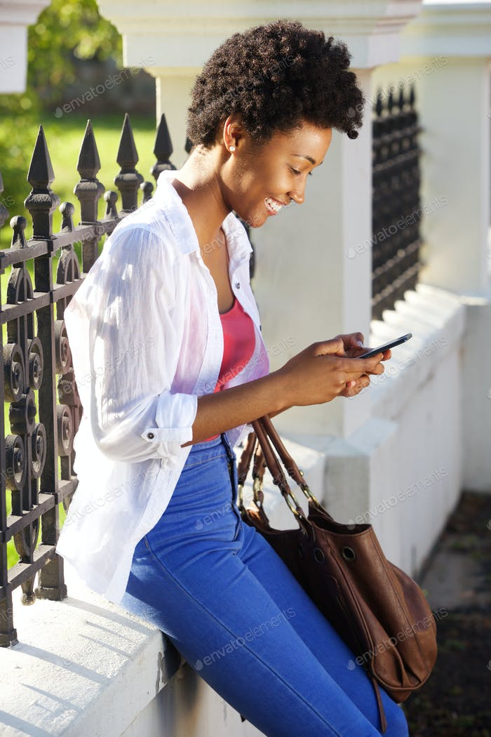 Happy young woman sitting outdoors and using mobile phone