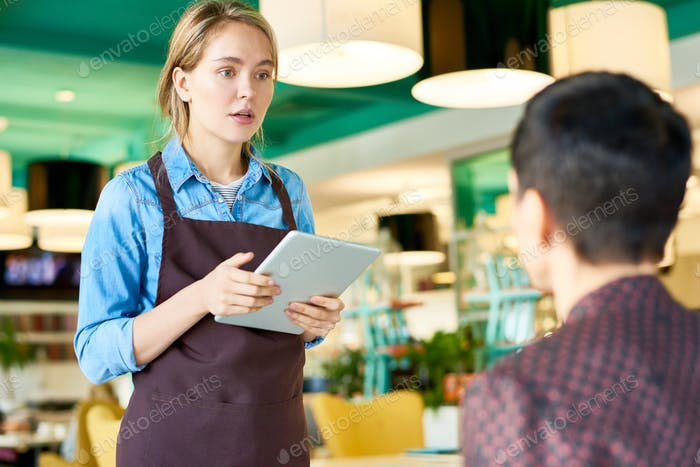 Young Waitress Taking Orders in Cafe