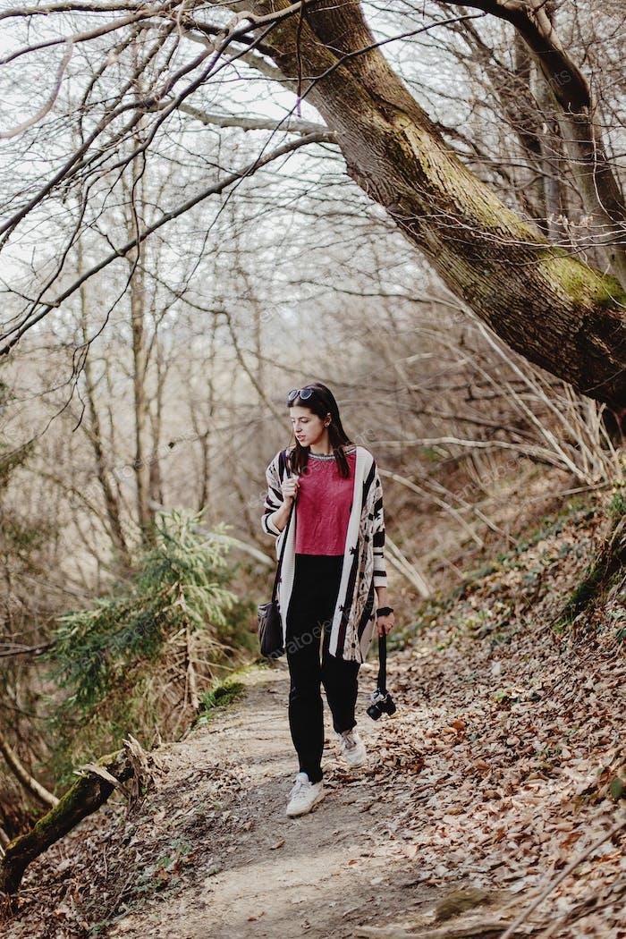 stylish hipster woman walking fashionable clothes with analog photo camera