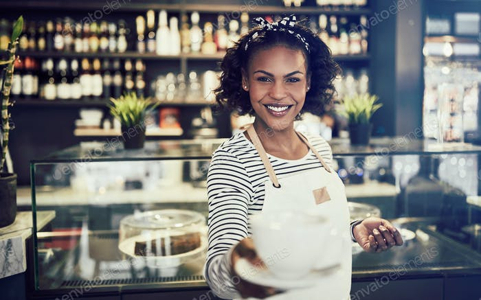 Smiling cafe waitress holding up a fresh cup of coffee