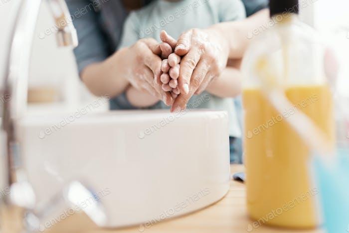 Kind und Erwachsene waschen sich die Hände.