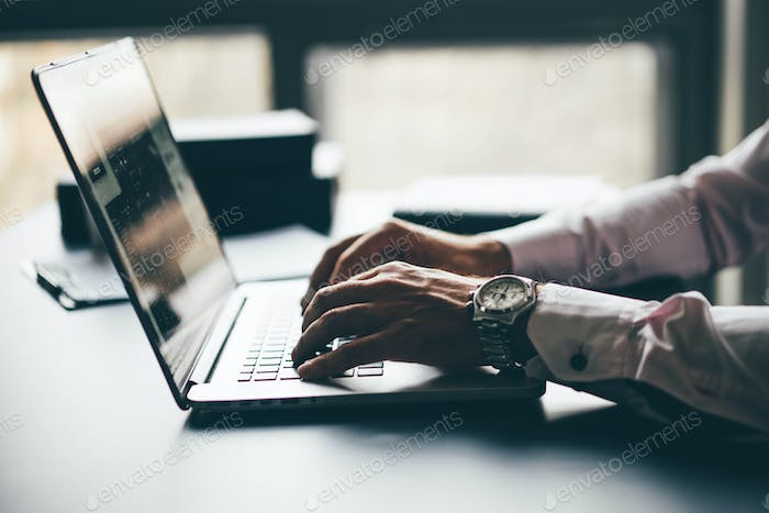 Young businessman working with laptop at modern office. Close up hand with notebook.