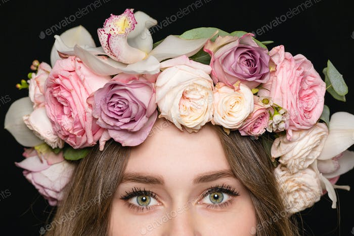 Closeup of woman eyes in beautiful rose wreath