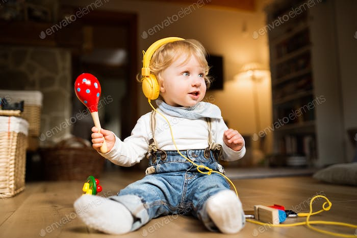 Little boy with earphones, listening music and plying musical in
