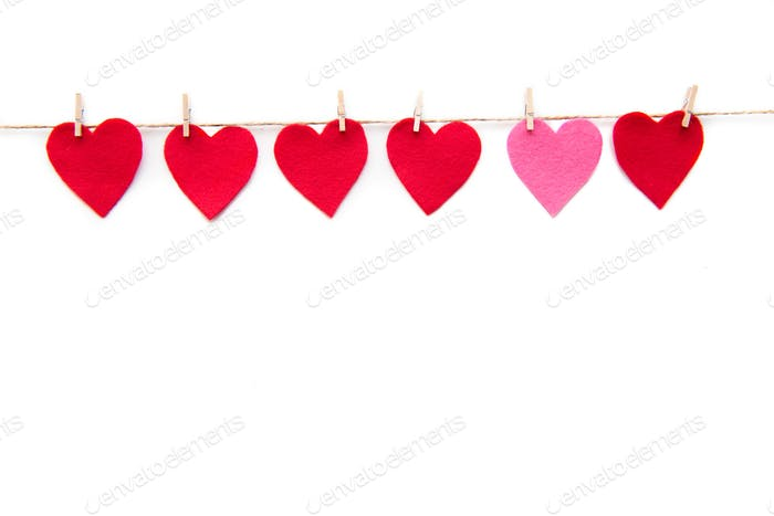 Red heart paper cut decorations hanging on clothespins isolated on white