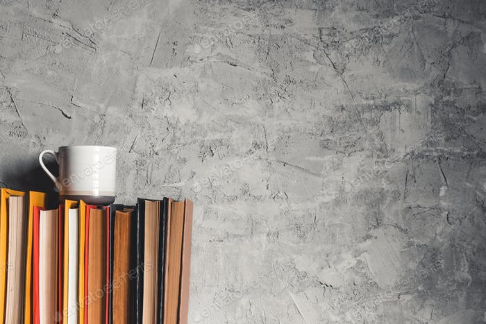 Eine Tasse Kaffee in der Nähe von Stapel Bücher auf grauem Hintergrund