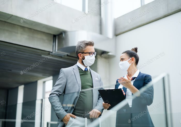 Flight attendant talking to businessman on airport, wearing face masks