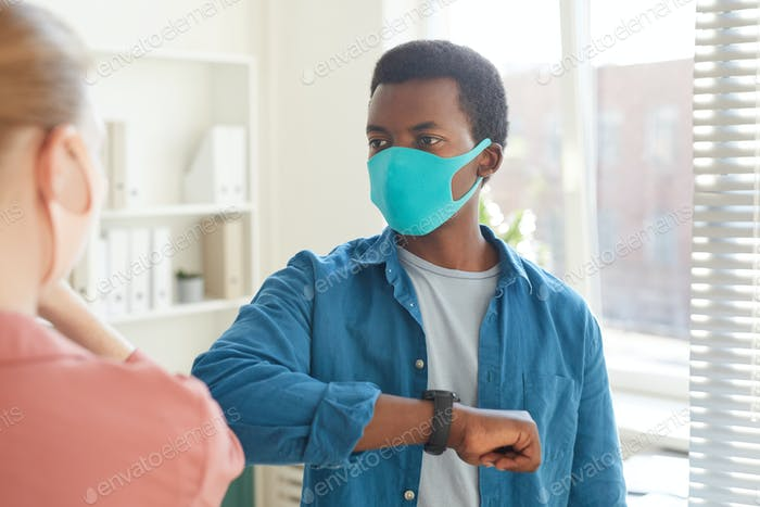 African Man Greeting Colleague in Post Pandemic Office