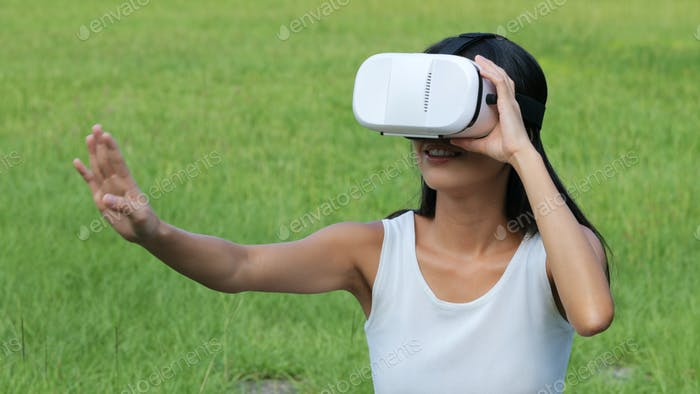 Woman watching with VR device and sitting at outdoor