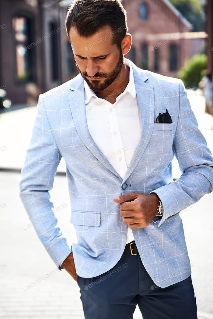 Portrait of handsome man in suit posing in the street