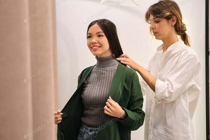Young fashion consultant helping trying on cardigan to pretty positive Asian girl in store