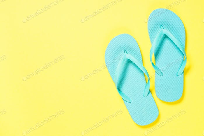 Blue flip flops on yellow background