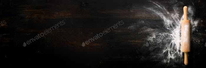Banner. Baking background with free space for your text. Rolling pin and flour on black table. Copy