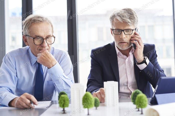 Shocked businessman talking by mobile phone during business meeting