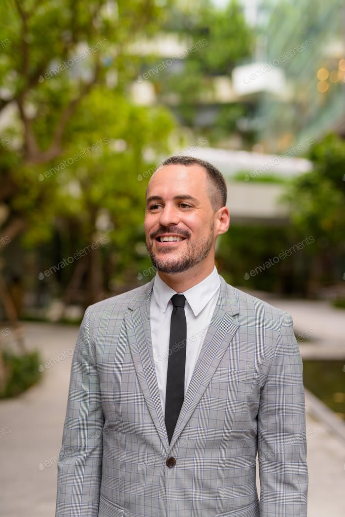 Happy Hispanic bald bearded businessman thinking with nature in the city outdoors