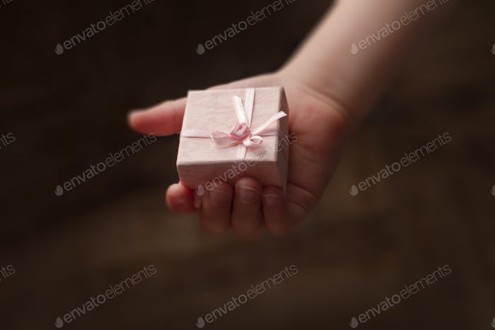 Hand of child holding a small pink gift box