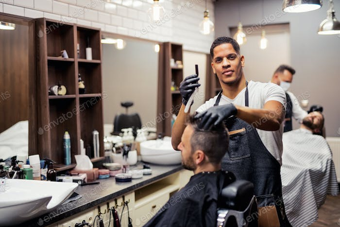A man client visiting haidresser and hairstylist in barber shop.