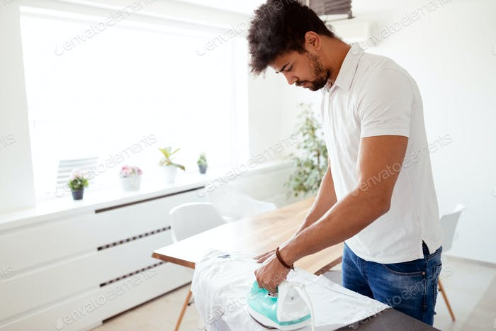 Man ironing shirt on ironing board