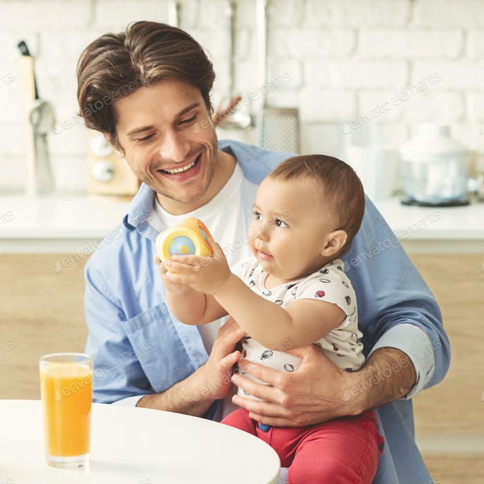 Cheerful daddy playing with his adorable baby at kitchen