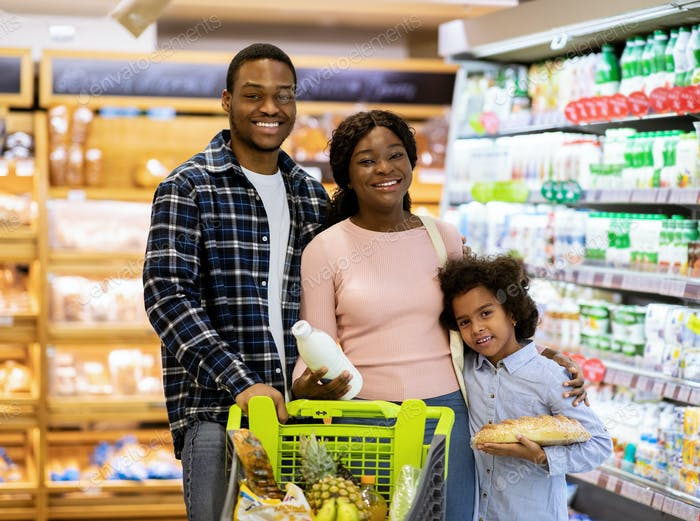 Portrait of happy African American parents with their daughter shopping for groceries at supermarket