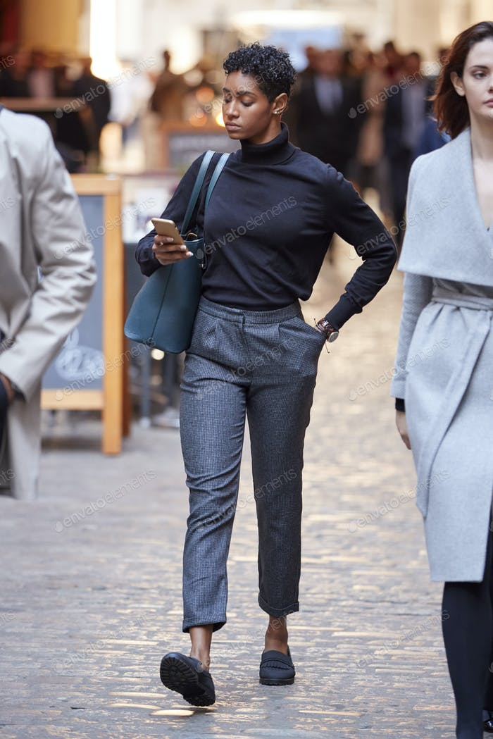 Young black businesswoman walking in the street in London using smartphone, selective focus
