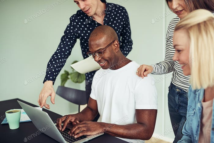 Smiling businesspeople working together on a laptop in an office