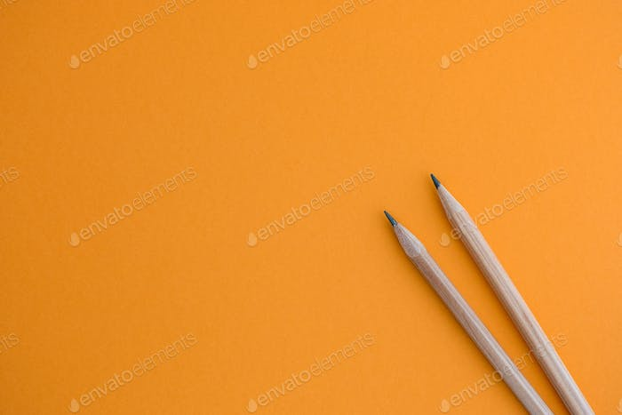 Two pencils on a yellow background.