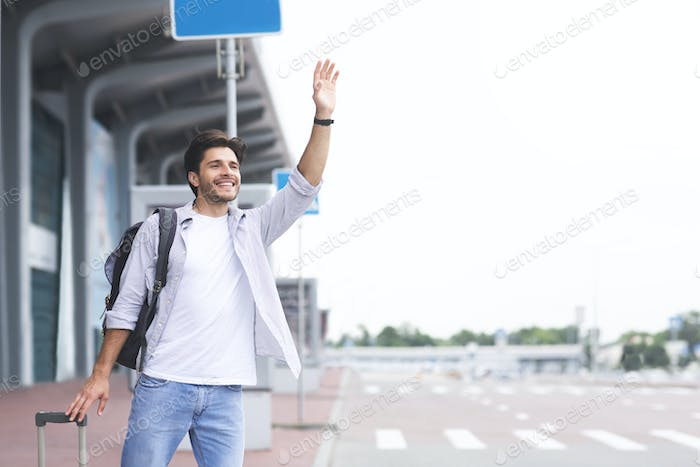 Young guy standing near airport, raising hand and trying to stop car