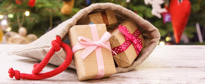 Heap of gifts with ribbons in bag for Christmas on background of christmas tree with decoration