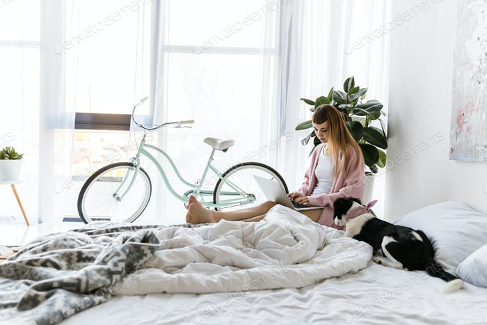 mujer joven usando el ordenador portátil en la mañana en casa