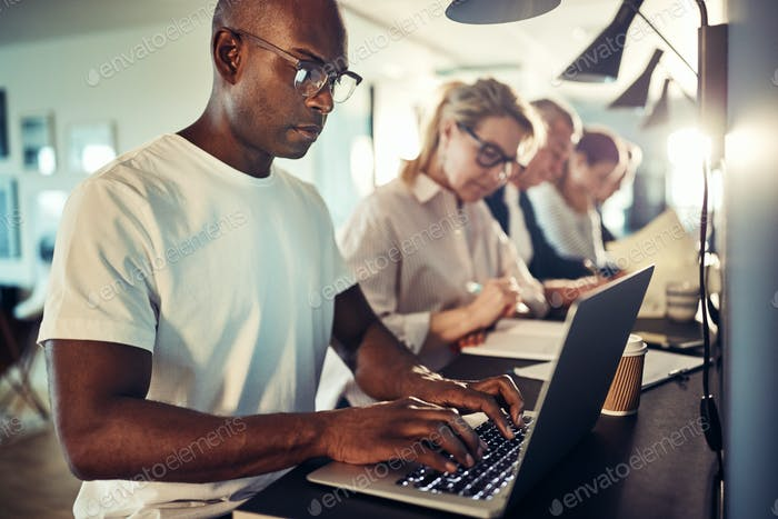 Young African designer working online with colleagues in the background