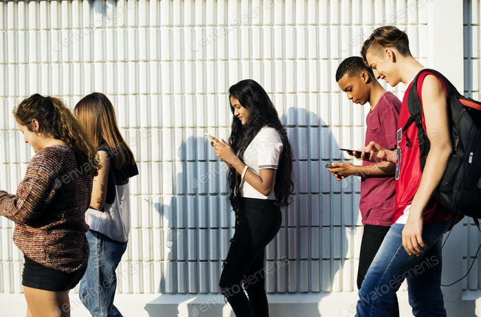 Group of young teenager friends walking home after school using smartphones addiction concept