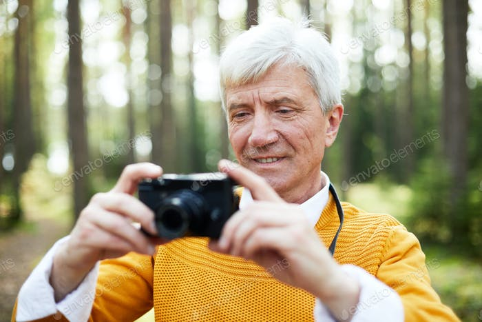 Content handsome senior photographing forest