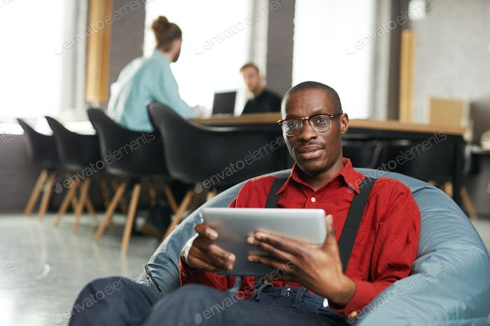 African -American Businessman Lounging in Office