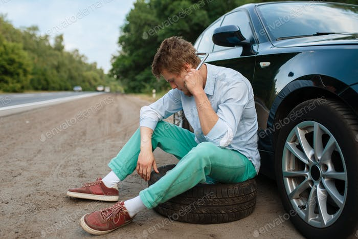 Car breakdown, young man sitting on spare tyre