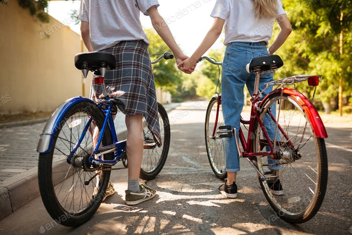Close up photo of man and woman bodies standing with red and blue bicycles and holding hands