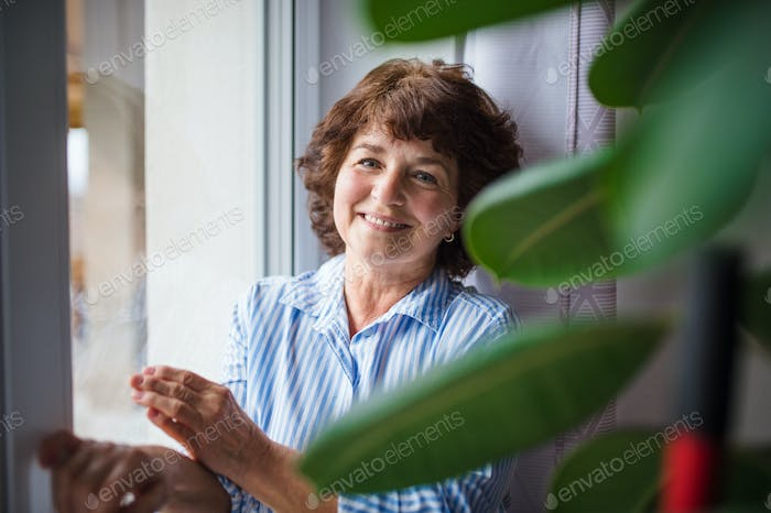Senior woman standing by window at home, relaxing