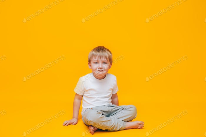 Crying little boy rubs his eyes with his hands, a boy in a white t-shirt on a yellow background
