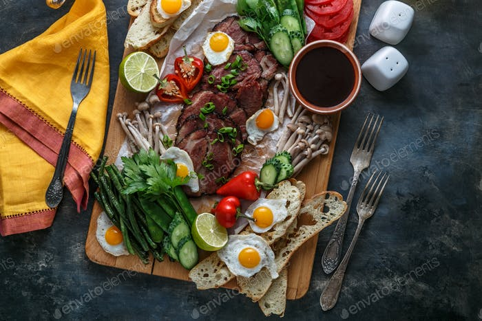 Breakfast with eggs, vegetables, bread, meat and tea, top view.