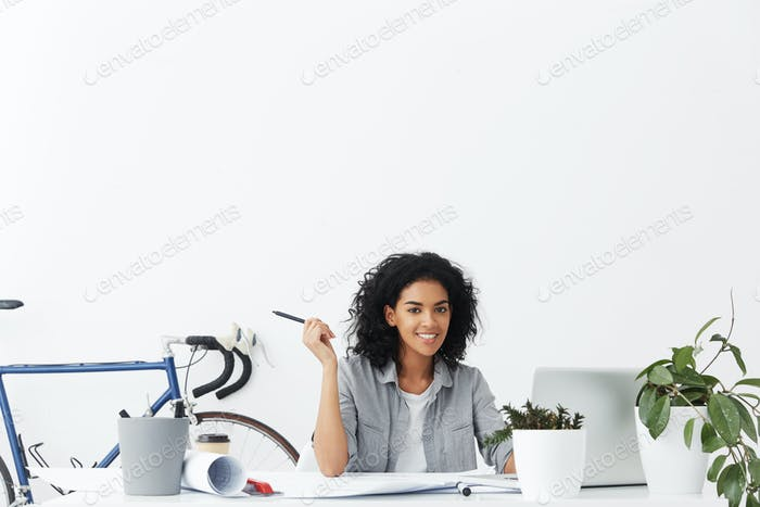 Cheerful woman architect holding pencil and turning off notebook pc at the end of working day after