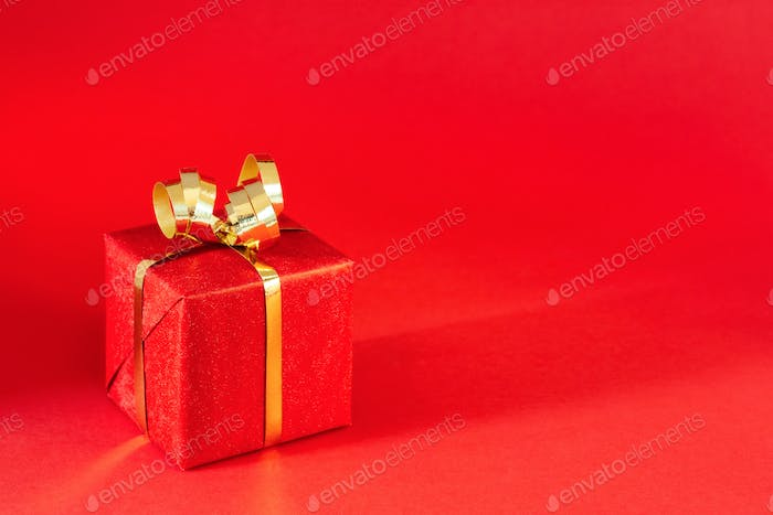 Red Gift Box with Golden Bow on Red Background.