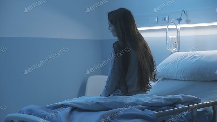 Sad sleepless patient sitting on the hospital bed at night
